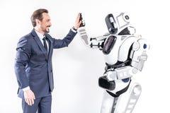 Joyeuse personne masculine faisant des amis avec le cyborg Photos stock