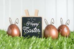 Joyeuses Pâques avec le lapin de griffonnage sur le tableau noir et le colo rose d'or Images stock