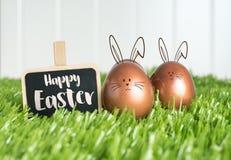 Joyeuses Pâques avec le lapin de griffonnage sur le tableau noir et le colo rose d'or Photographie stock libre de droits