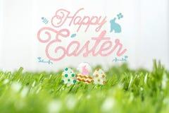 Joyeuses Pâques avec le lapin en verre eggs sur le champ d'herbe verte au petit morceau Photo stock