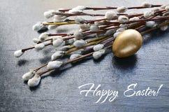 Joyeuses Pâques Branches de saule et oeuf de pâques sur un fond foncé Saule de chat et oeuf d'or Photographie stock