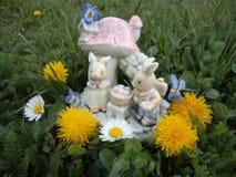Joyeuses Pâques ! Lapins avec des oeufs de pâques devant le cottage Photos libres de droits