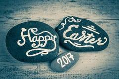 Joyeuses Pâques 2017 lettres écrites sur des cailloux dans le noir et le petit morceau Images libres de droits
