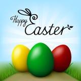 Joyeuses Pâques Oeufs avec l'herbe verte Ciel bleu avec des rayons comme fond Photo stock