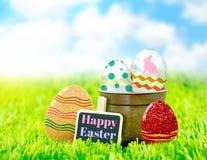 Joyeuses Pâques sur le panneau d'agrafe noir avec les oeufs de pâques colorés sur le GR Images stock