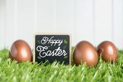 Joyeuses Pâques sur le tableau noir et or rose colorent des oeufs de pâques sur le GR Images libres de droits