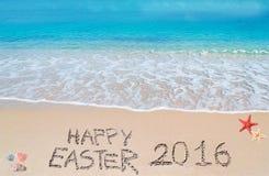 Joyeuses Pâques 2016 sur une plage tropicale sous des nuages Images libres de droits