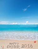 Joyeuses Pâques 2016 sur une plage tropicale sous des nuages Photos stock