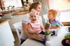 Joyeuses Pâques Une mère et ses enfants peignant des oeufs de pâques photo stock