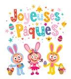 Joyeuses Paques Pascua feliz en tarjeta de felicitación francesa con los conejitos de pascua lindos de los niños Fotos de archivo libres de regalías