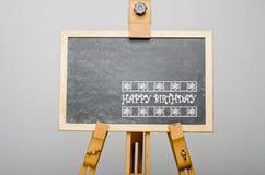 Joyeux anniversaire écrit sur le tableau noir, peinture de chevalet Photographie stock