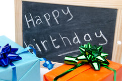 Joyeux anniversaire écrit sur un tableau noir d'ardoise avec des cadeaux Images stock