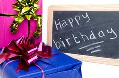 Joyeux anniversaire écrit sur un tableau noir d'ardoise avec des cadeaux Photos stock