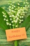 Joyeux anniversaire et bouquet des lis frais sensibles de la vallée Image libre de droits