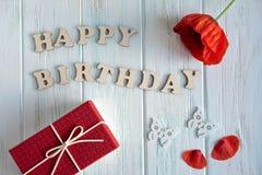 Joyeux anniversaire Salutation de l'inscription des lettres en bois sur un fond en bois clair avec un cadeau, une fleur de pavot  photographie stock libre de droits