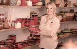 Joyeux client féminin sélectionnant la vaisselle vitrée par rouge images stock