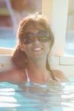 Joyeux et loisirs Femme de sourire avec des lunettes de soleil des vacances à la piscine Photos libres de droits
