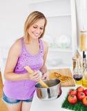 Joyeux femme faisant cuire des spaghetti à la maison Image libre de droits
