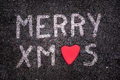 Joyeux Noël écrit sur la route goudronnée, pierre rouge sous forme de coeur Photos stock