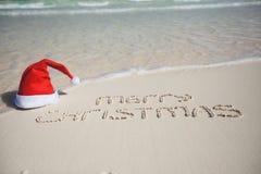 Joyeux Noël écrit sur le blanc tropical de plage Images libres de droits