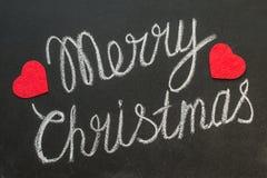 Joyeux Noël écrit sur un tableau noir avec la craie Photos libres de droits
