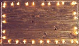 Joyeux Noël ! Cadre de lumières de Noël sur le fond en bois avec l'espace de copie photo stock