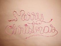 Joyeux Noël d'écriture fait en corde rouge et blanche de colis dessus photographie stock libre de droits