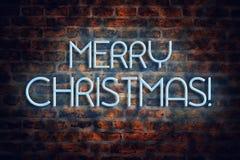 Joyeux Noël d'inscription au néon sur un fond de mur de briques Fond de Noël image stock
