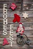 Joyeux Noël dans les lettres allemandes avec Santa dans d rouge et en bois Image stock