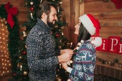 Joyeux Noël et bonne année Jeunes couples célébrant des vacances à la maison Le jeune homme et la femme se tiennent vis-à-vis de  Images libres de droits
