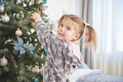 Joyeux Noël et bonnes fêtes jeune fille aidant décorant l'arbre de Noël, tenant quelques babioles de Noël dedans Photos libres de droits