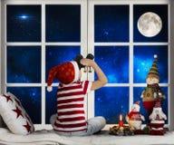 Joyeux Noël et bonnes fêtes ! L'enfant s'assied sur le filon-couche de fenêtre et regarder par des jumelles L'enfant apprécient l image libre de droits