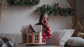 Joyeux Noël et bonnes fêtes La jeune femme boivent du thé chaud avec des biscuits de Noël banque de vidéos