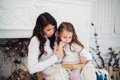Joyeux Noël et bonnes fêtes, maman assez jeune lisant un livre à sa fille mignonne près de l'arbre à l'intérieur Photographie stock