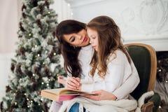Joyeux Noël et bonnes fêtes, maman assez jeune lisant un livre à sa fille mignonne près de l'arbre à l'intérieur Photographie stock libre de droits