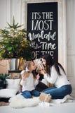 Joyeux Noël et bonnes fêtes Maman gaie et sa fille mignonne de fille ouvrant un cadeau de Noël Parent et photographie stock libre de droits