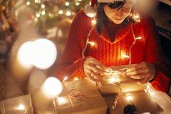 Joyeux Noël fille enveloppant des cadeaux de Noël dans les lumières dans e photos libres de droits