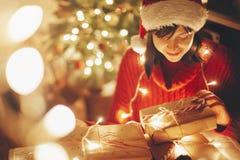 Joyeux Noël fille enveloppant des cadeaux de Noël dans les lumières dans e photos stock