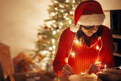 Joyeux Noël fille enveloppant des cadeaux de Noël dans les lumières dans e images stock