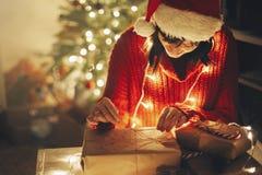 Joyeux Noël fille enveloppant des cadeaux de Noël dans les lumières dans e images libres de droits