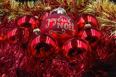 Christmas balls red and gold. `Joyeux Noël`, `Happy Christmas`, Red and gold Christmas balls on a background of gold and red Royalty Free Stock Photo