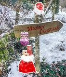 Joyeux Noël sur un poteau de signal de direction décoré d'une boule de Noël de chapeau du père noël et d'un sac avec des présents photo stock