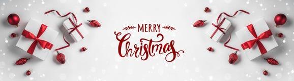 Joyeux Noël typographique sur le fond blanc avec les boîte-cadeau et la décoration rouge photo stock