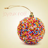 Joyeux noel, merry christmas in french. A christmas ball coated with nonpareils of different colors and the sentence joyeux noel, merry christmas written in Stock Photography
