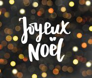Joyeux noel text. Holiday greetings. Merry Christmas french quote. Glowing lights on dark blurred background. Joyeux noel text - french Merry Christmas quote Stock Image