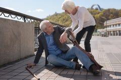 Joyeux retraité s'asseyant sur la rue et recevant l'aide Photographie stock