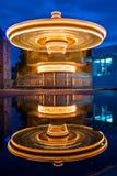 Joyeux vont le rond la nuit en parc d'attractions avec la réflexion photos stock