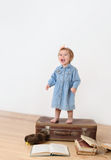 Joyfool little girl standing on a suitcase Royalty Free Stock Photos