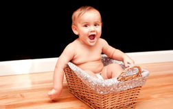 Joyful 9 month old baby in basket Royalty Free Stock Photos