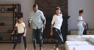 Joyful active african american family dancing jumping in living room